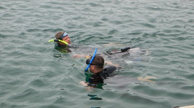 Divers tow an AUV back to the starting gate